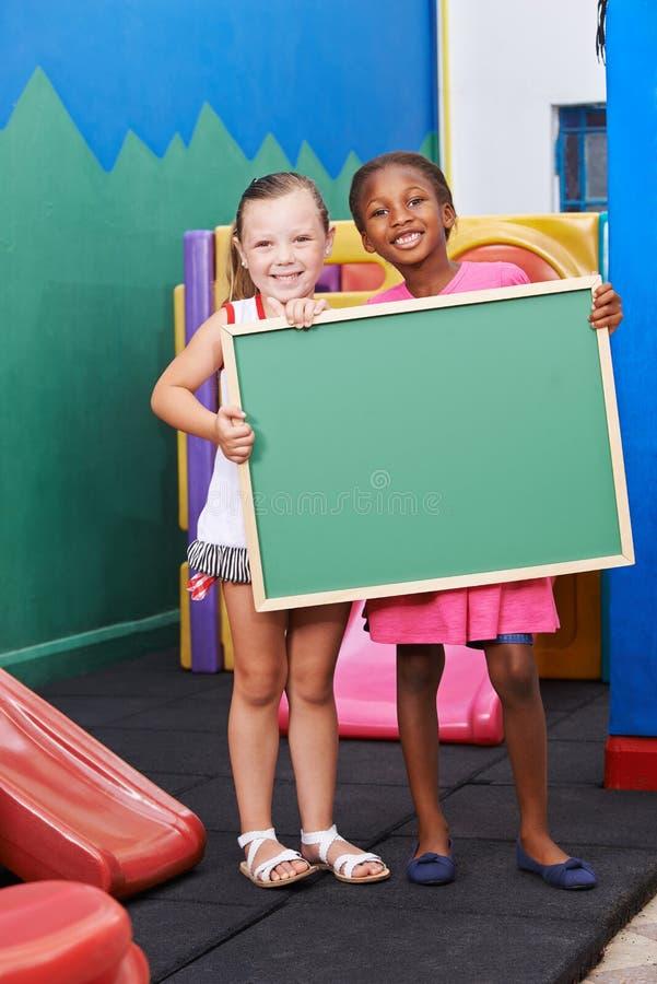 Barn som rymmer den tomma svart tavla i dagis royaltyfria foton