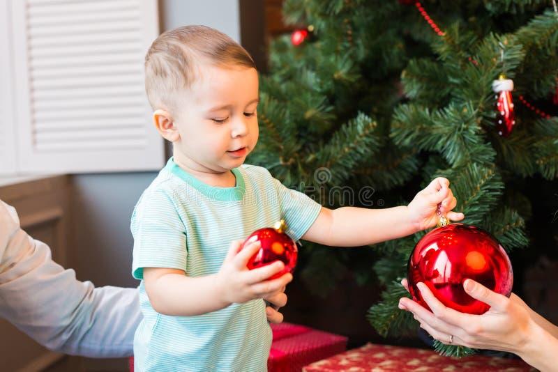 Barn som rymmer en röd julgarnering royaltyfri foto