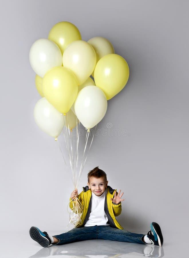 Barn som rymmer gruppen av ballonger som blir på knäet över den vita bakgrunden royaltyfria foton
