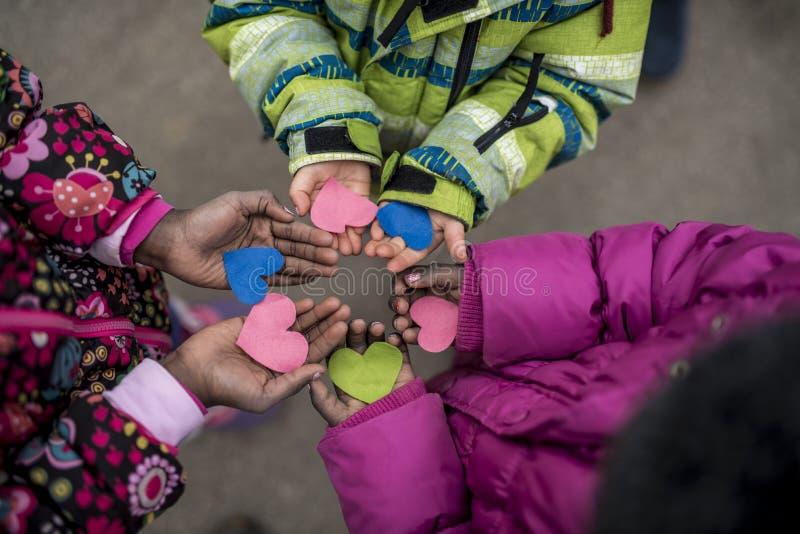 Barn som rymmer hjärtor i händer arkivfoton