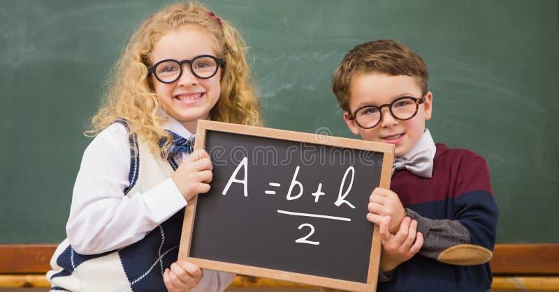 Barn som rymmer svart tavla med matematiklikställande royaltyfria foton