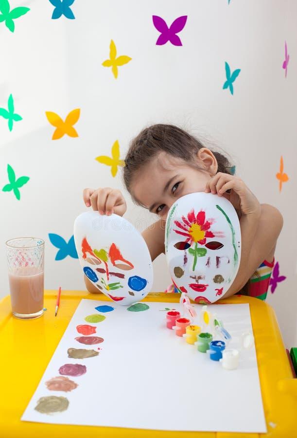 Barn som rymmer två målade maskeringar arkivfoto