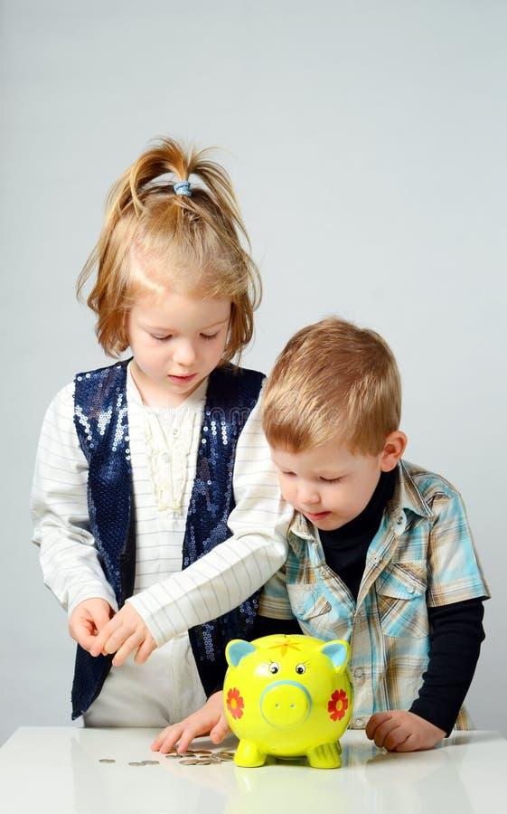 Barn som sätter deras besparingar till en spargris royaltyfri bild