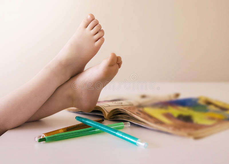 Barn som sätter deras fot, upp når lyckat att ha färgat en bild i en bok royaltyfri foto