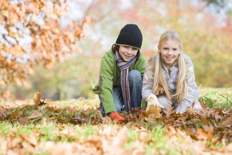 barn som samlar leaves två royaltyfria foton