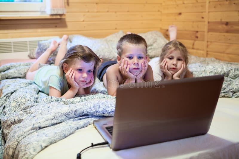 Barn som ser bärbar datorbildskärmen, innan att sova arkivfoto