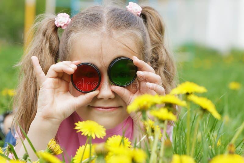 Barn som ser till och med kulört exponeringsglas (fotofilter) på dandeli royaltyfri foto