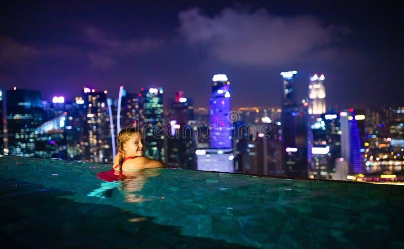 Barn som simmar i bästa utomhus- pöl för tak på familjsemester i Singapore Stadshorisont från oändlighetspöl i lyxigt hotell unga arkivbilder