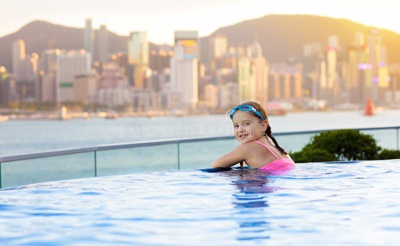 Barn som simmar i utomhus- pöl för taköverkant på familjsemester i Hong Kong Stadshorisont från oändlighetspöl i lyxigt hotell in royaltyfria foton