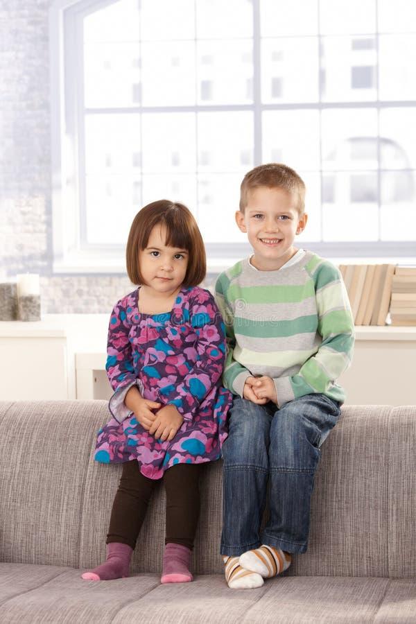 barn som sitter den le sofaen royaltyfri fotografi