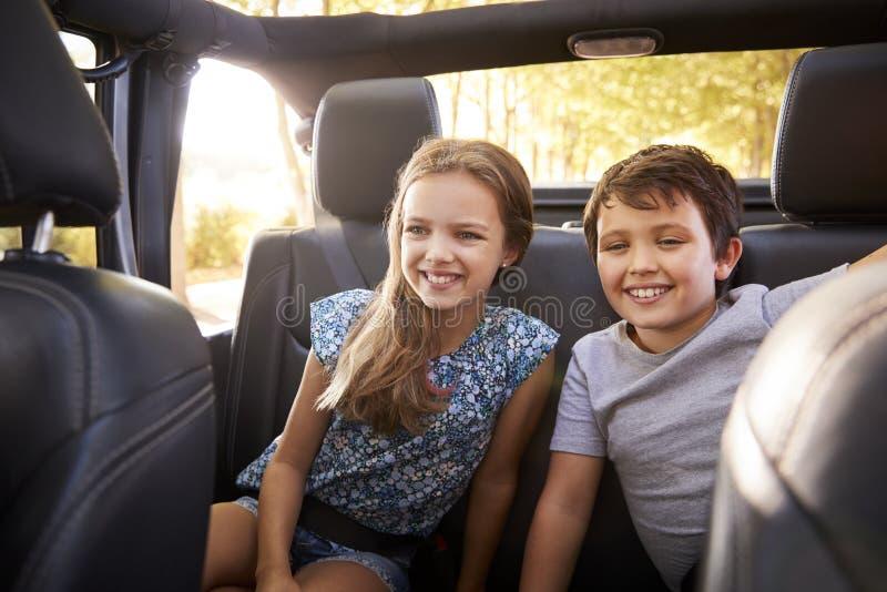 Barn som sitter i baksäte av den öppna bästa bilen på vägtur royaltyfri bild