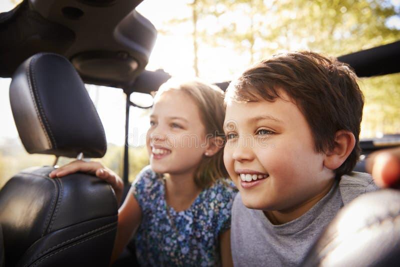Barn som sitter i baksäte av den öppna bästa bilen på vägtur arkivbilder