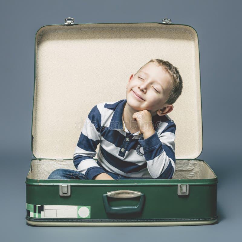 Barn som sitter i en gammal resväska leende som föreställer sig en resa fotografering för bildbyråer