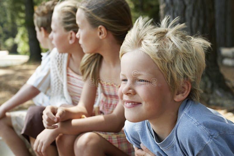 Barn som sitter i skog royaltyfria foton