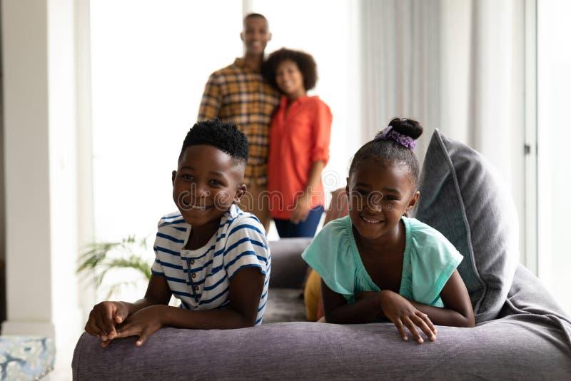 Barn som sitter på en soffa medan deras föräldrar som står i bakgrunden royaltyfria foton