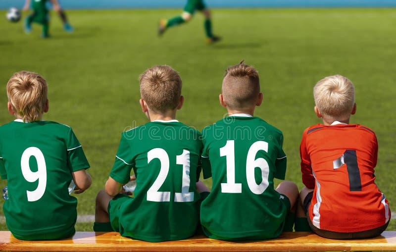 Barn som sitter på fotbollfotbollträbänk Ungar Junior Football Team arkivfoton