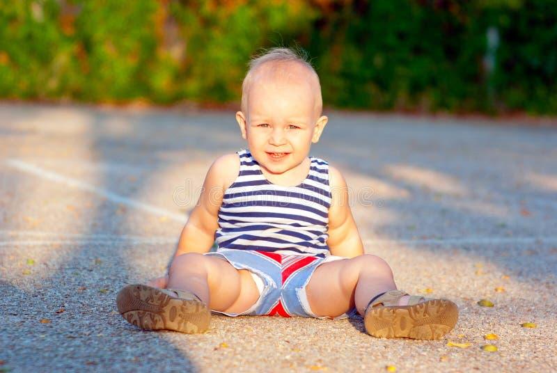 Barn som sitter på jordningen arkivfoton