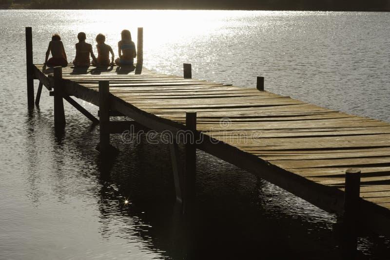 Barn som sitter på kanten av bryggan på sjön arkivfoto