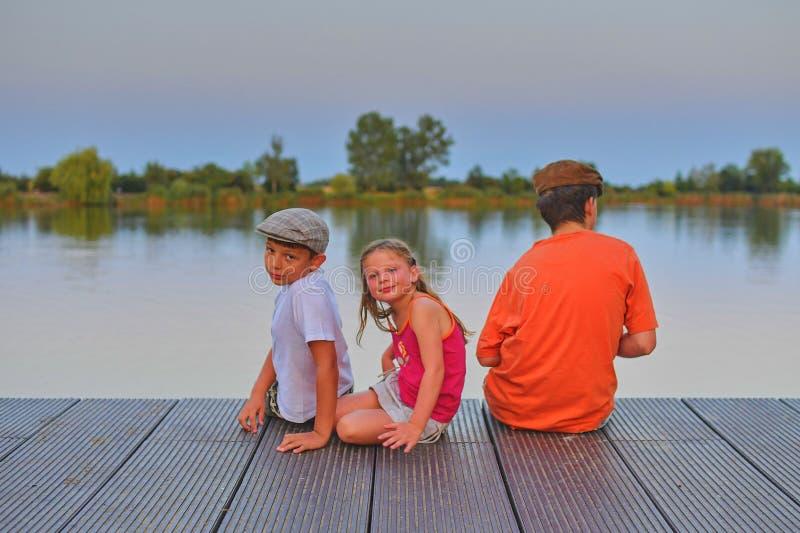 Barn som sitter på pir syskon Tre barn av olik ålder - tonåringpojke, elementär ålderpojke och förträningsflickasammanträde royaltyfria foton