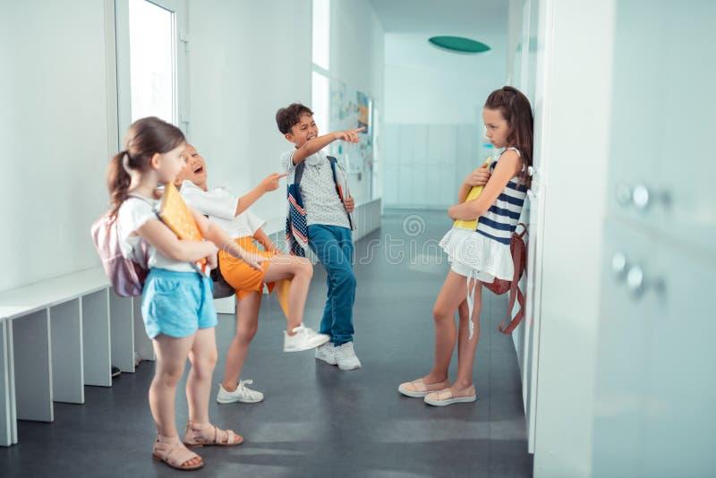 Barn som skrattar och trakasserar deras nya klasskompis royaltyfria bilder
