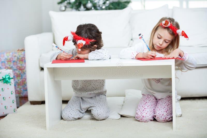 Barn som skrivar brevet till Santa Claus During fotografering för bildbyråer