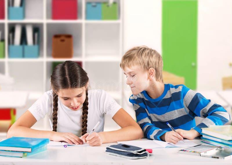 Barn som skriver ett prov arkivfoto