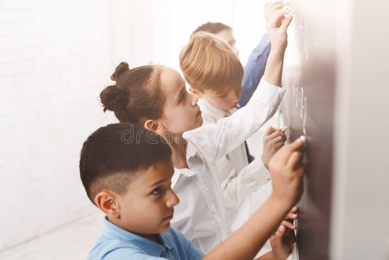 Barn som skriver matematiklikställande på brädet royaltyfri foto