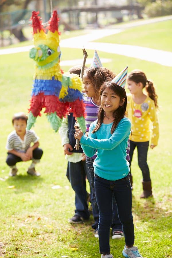 Barn som slår Pinata på födelsedagpartiet arkivbilder