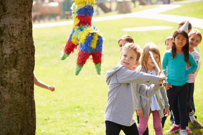 Barn som slår Pinata på födelsedagpartiet royaltyfria foton
