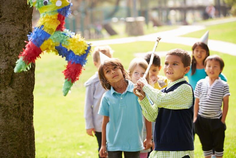 Barn som slår Pinata på födelsedagpartiet royaltyfri bild