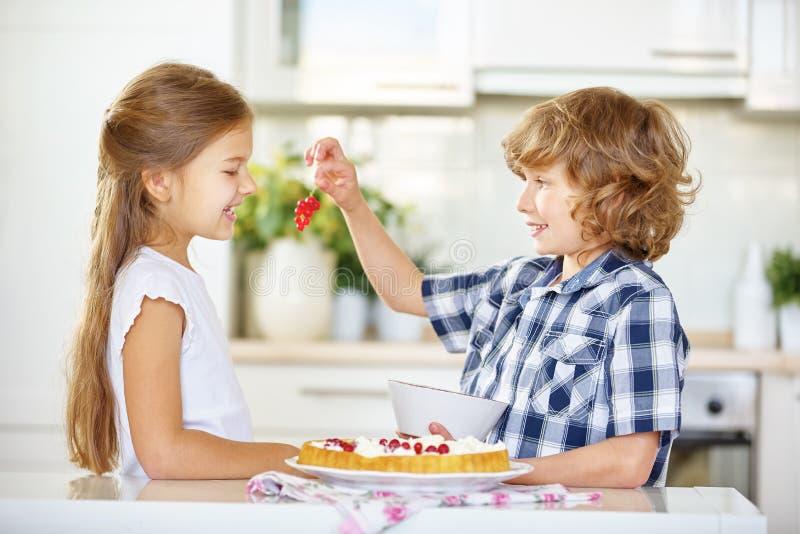Barn som smakar röda vinbär, medan baka arkivfoton