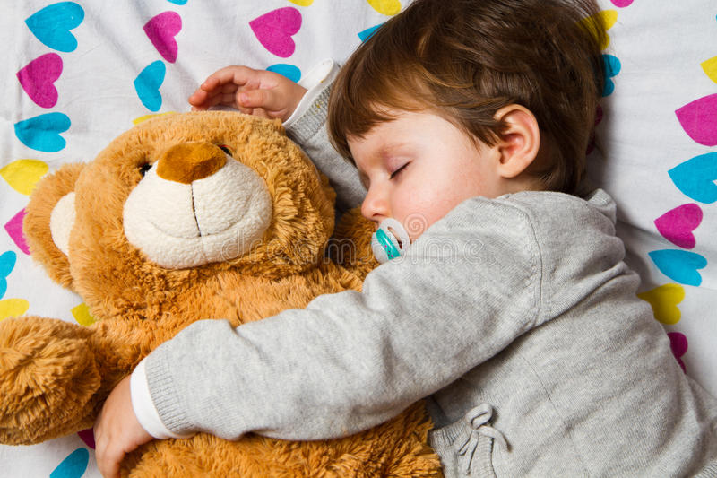 Barn som sovar med nallebjörnen royaltyfria bilder
