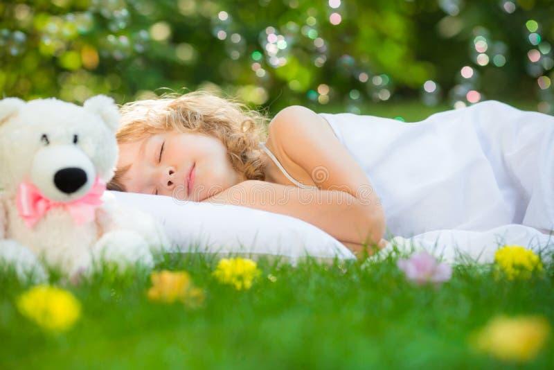 Barn som sover i vårträdgård royaltyfria foton