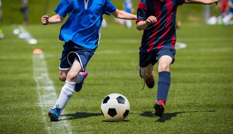 Barn som sparkar fotbollsmatchen på gräs Ungdomfotbolllek pojke royaltyfria bilder