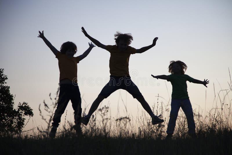 Barn som spelar banhoppning på den silhouetted sommarsolnedgångängen royaltyfria bilder