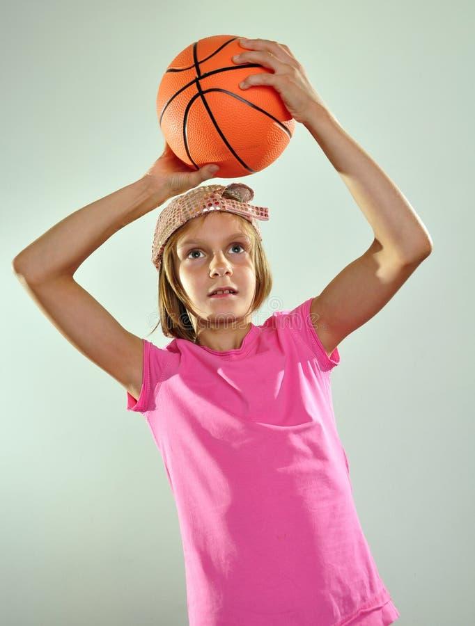 Barn som spelar basket och kastar bollen arkivfoton