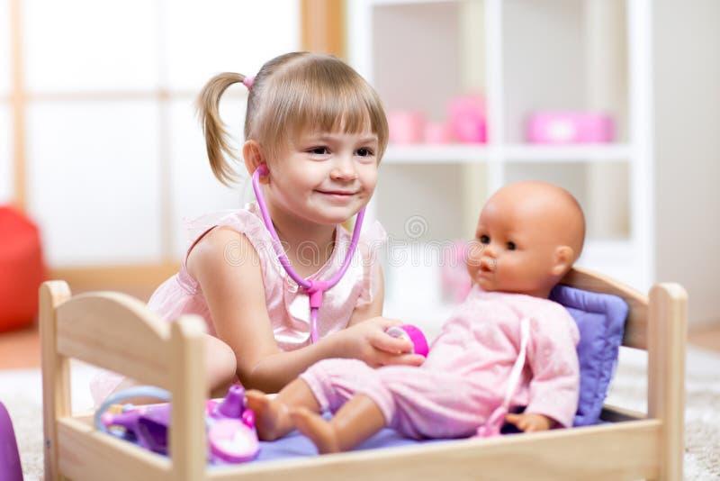 Barn som spelar doktorn med dockaleksaken royaltyfri bild