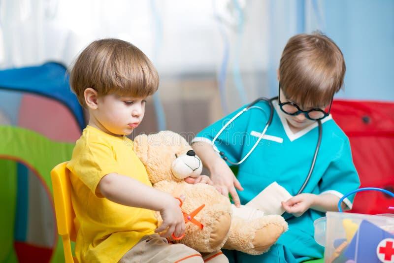Barn som spelar doktorn och hemma kurerar den flotta leksaken arkivfoton