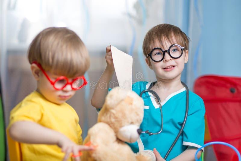 Barn som spelar doktorn och inomhus kurerar den flotta leksaken fotografering för bildbyråer