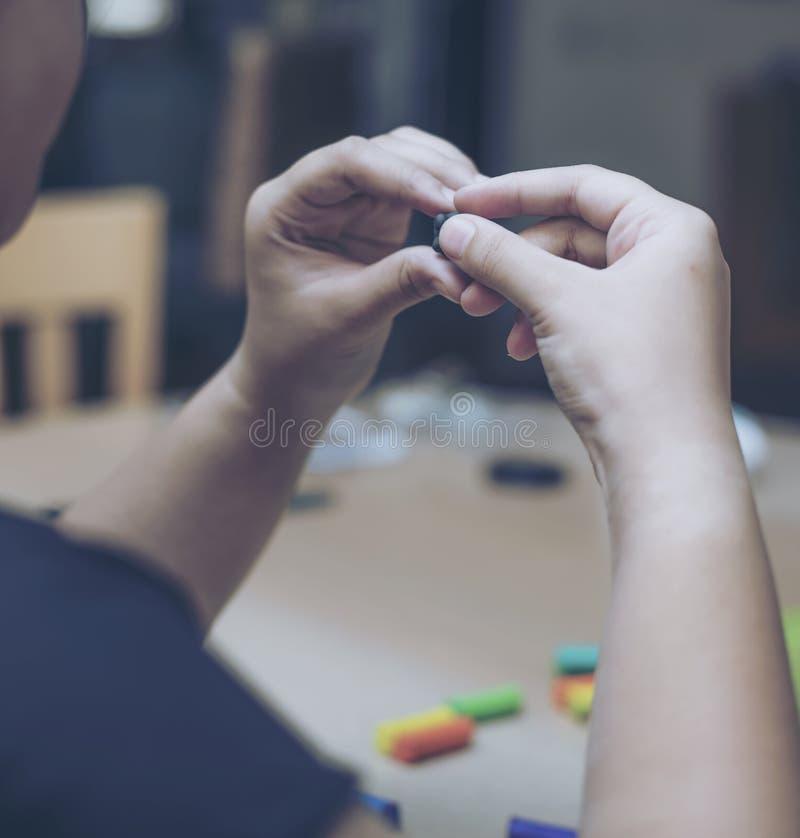 Barn som spelar färgrik lera på den wood tabellen arkivfoton