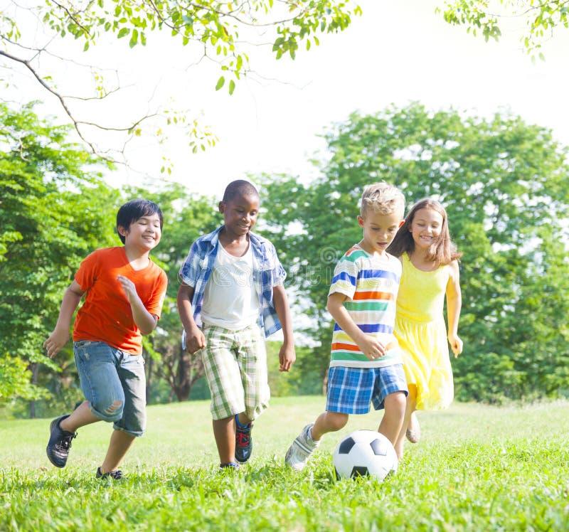 Barn som spelar fotboll i parkera arkivfoton