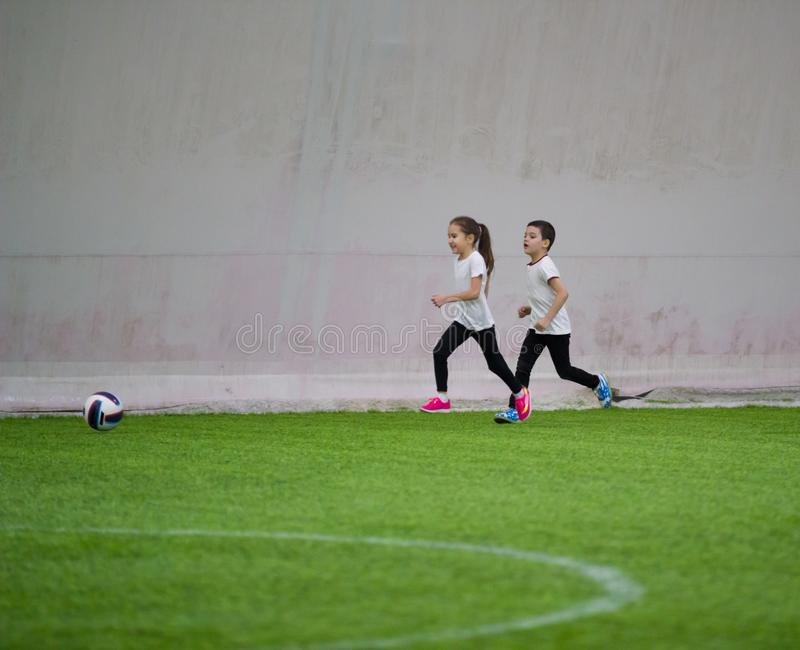 Barn som spelar fotboll inomhus Lite spela för flicka och för pojke royaltyfria bilder