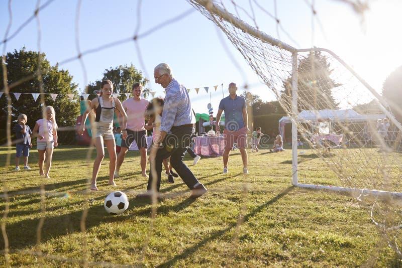 Barn som spelar fotbollsmatchen med stor fest för trädgård för faderAnd Grandfather At sommar arkivbild