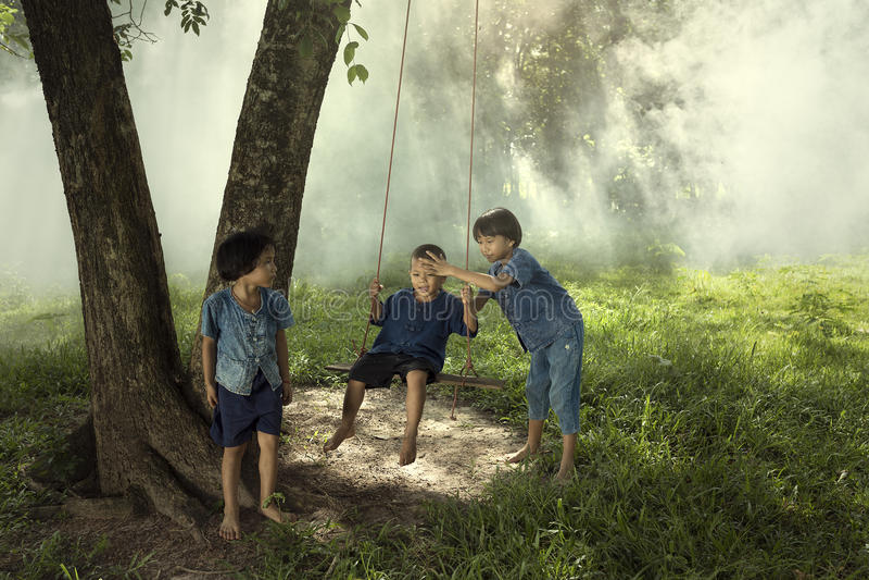 Barn som spelar gunga arkivfoton
