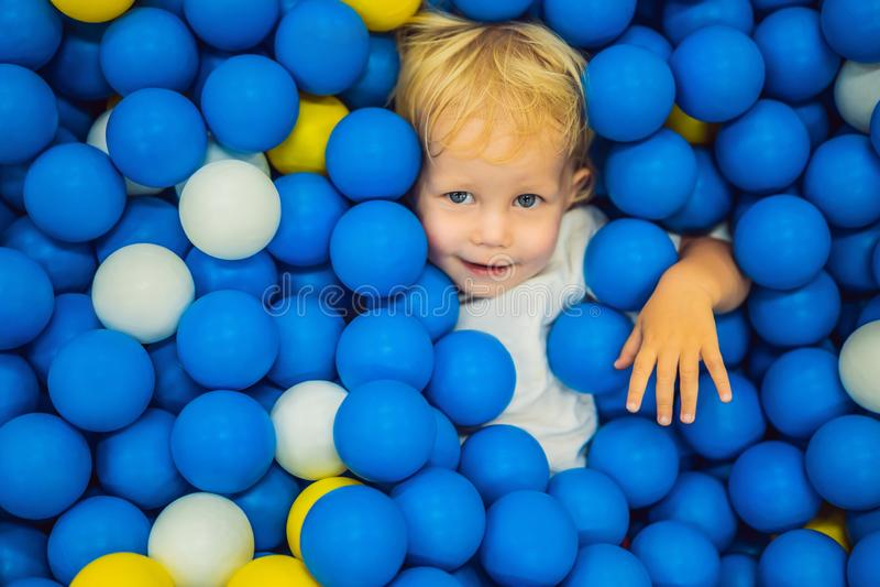 Barn som spelar i bollgrop F?rgrika leksaker f?r ungar Dagis eller f?rskole- lekrum Litet barnunge p? daghem inomhus arkivbild