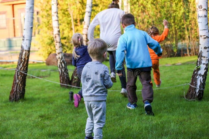 Barn som spelar i en trädgård arkivfoton