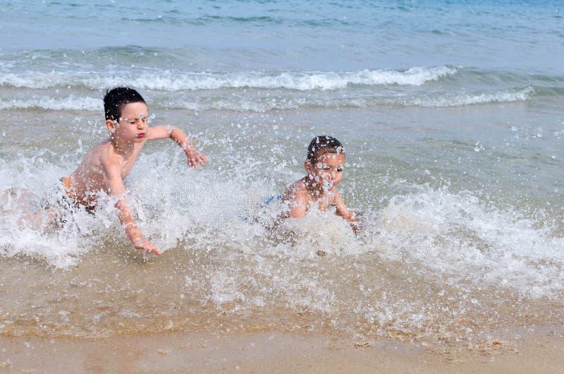 Barn som spelar i havsvågor arkivbild