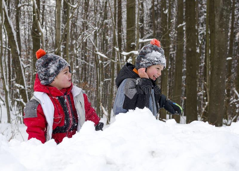 Barn som spelar i insnöad vinter arkivbild