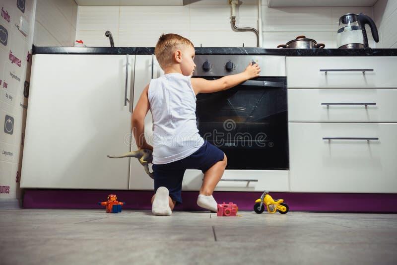 Barn som spelar i köket med en gasugn fotografering för bildbyråer