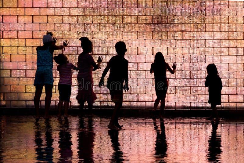 Barn som spelar i kronaspringbrunn fotografering för bildbyråer
